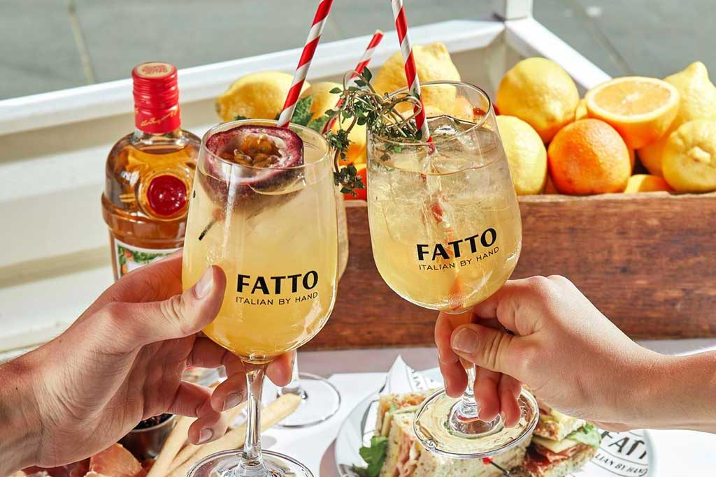 2 Fatto cocktail glasses are being clinked over a spread of food