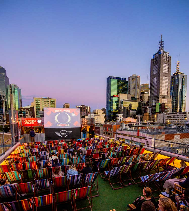 People sitting in deck chairs on a rooftop in front of a big screen