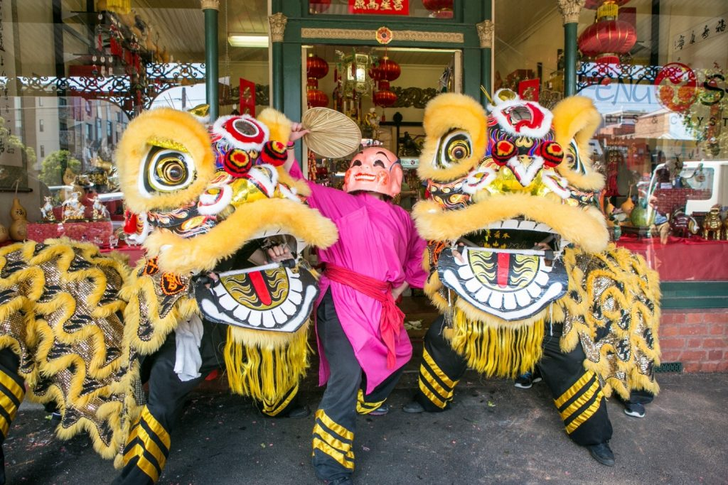 Large yellow puppet lions and man in mask outside shop with lanterns in window