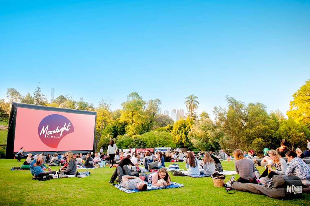 A group of people sitting on rugs in a park in front of a big outdoor screen