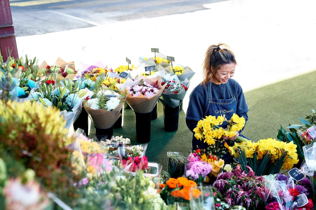 Bunches of flowers in buckets at an outdoor shop with smiling person wearing apron