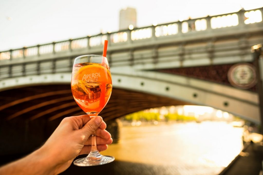 A hand holding a cocktail with a river and a bridge in the background
