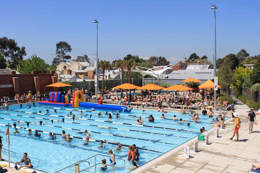 People swimming in an outdoor pool on a sunny day