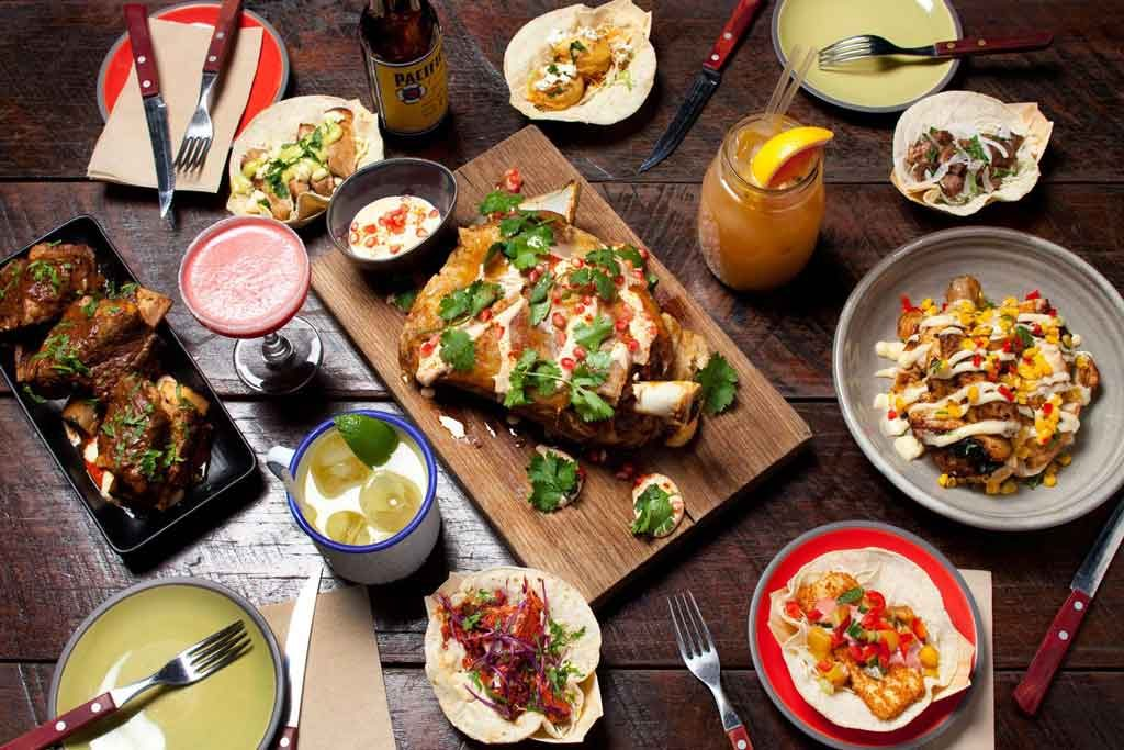 A flat lay of Mexican food on wooden boards