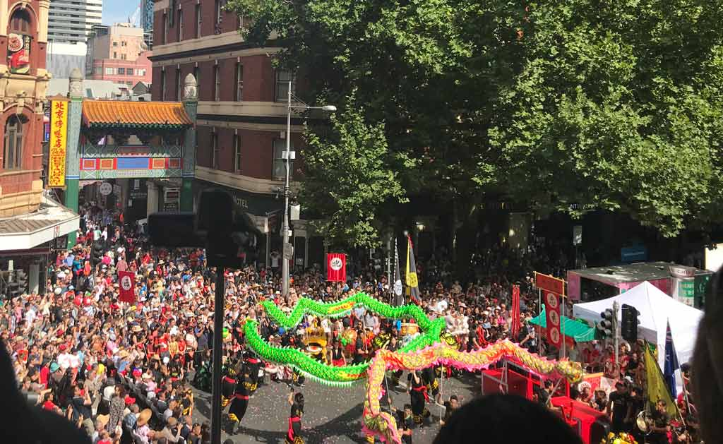 A huge crowd around a performing Chinese dragon