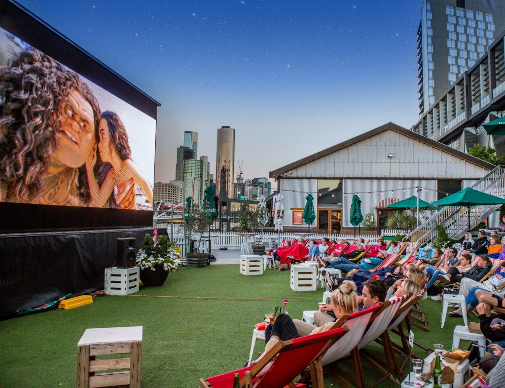 People sitting on deck stairs watching a movie on a big screen outdoors