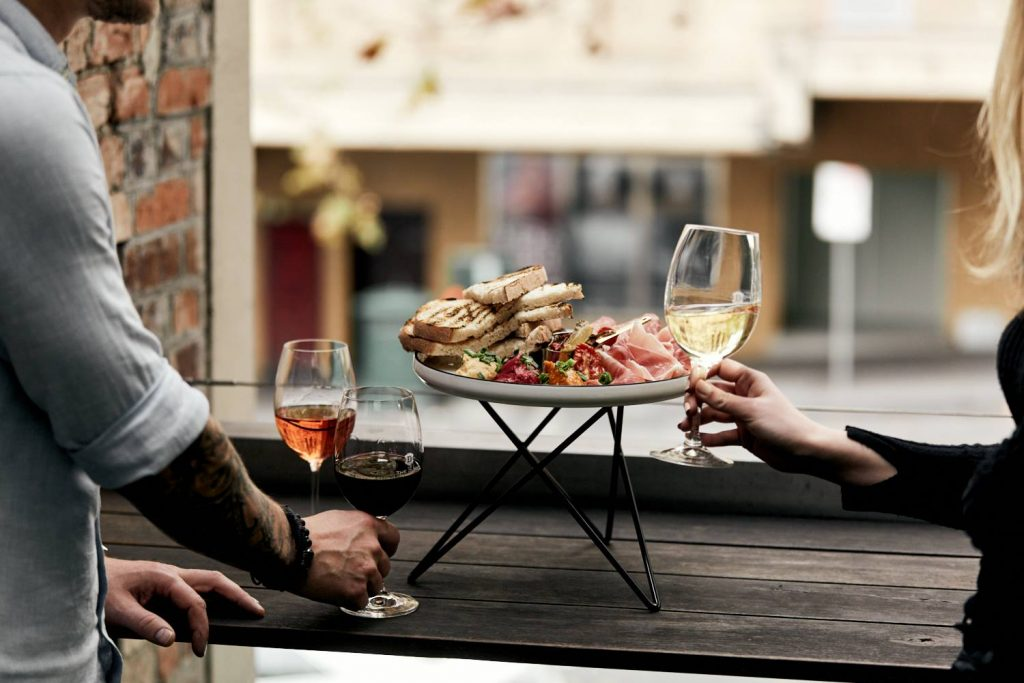 Two hands holding glasses of wine next to a platter of cured meats, cheeses and bread with a view of a city street in the background