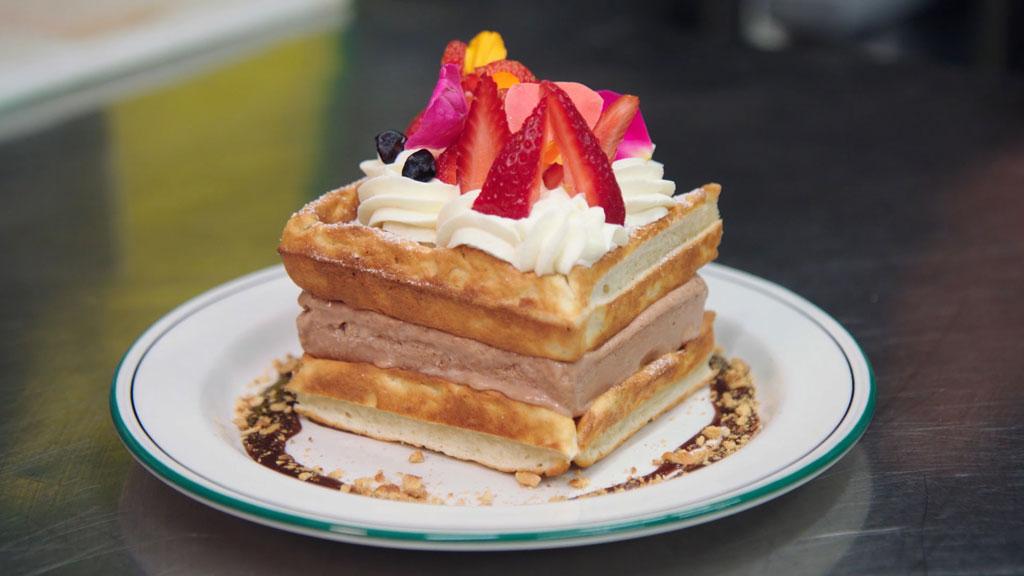A waffled icecream sandwich on a white plate