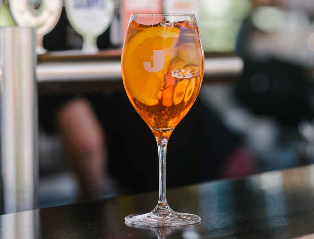 A spritz cocktail on a bar bench