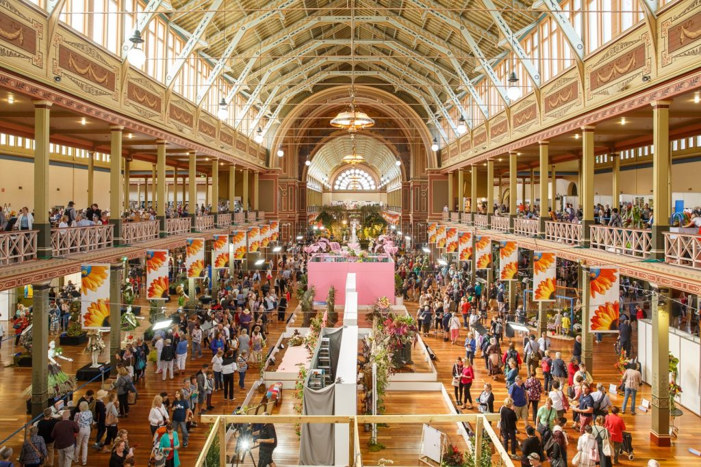The interior of a large exhibition building with an event going on