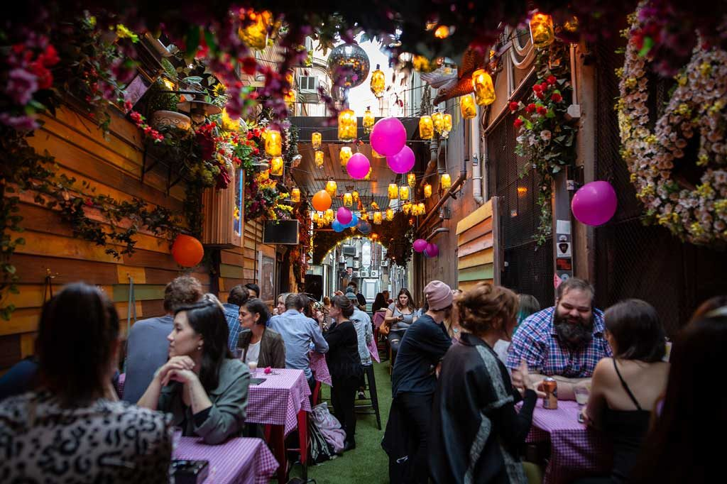 A narrow laneway bar with lights and flowers hanging across the roof