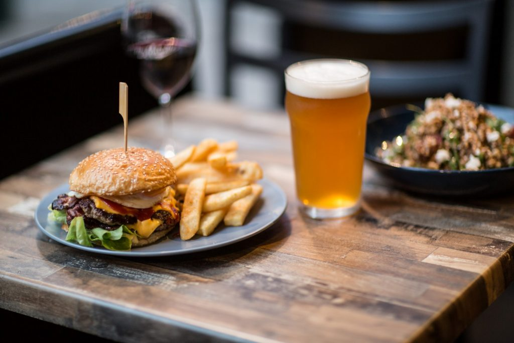 A burger on a plate with chips, a glass of beer beside it