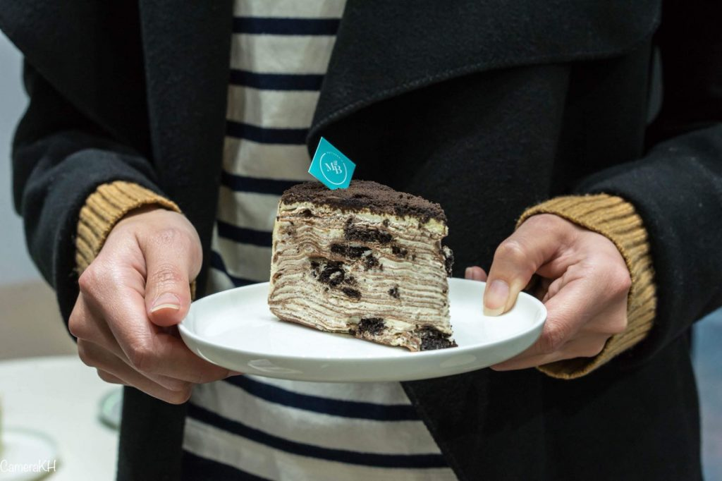 A multi-layered crepe cake with cookies and cream in it