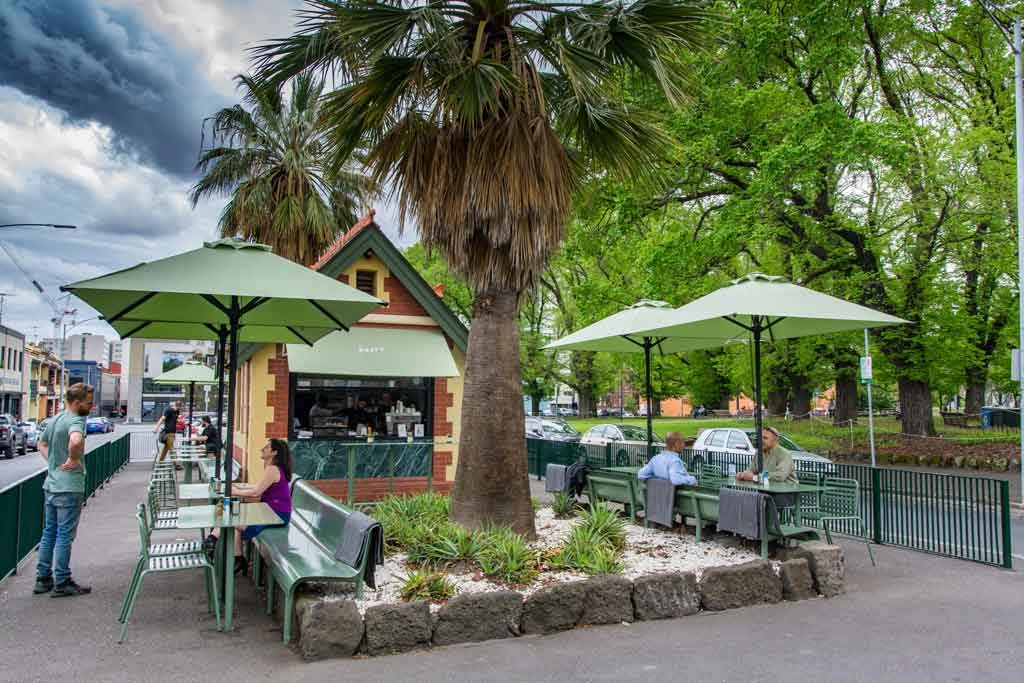 A small cafe surrounded by trees and outdoor umbrellas