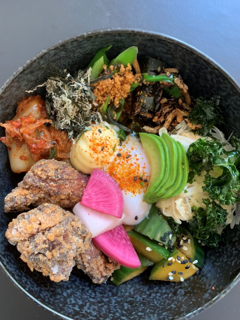 A black bowl filled with veggies, fried chicken and pickles