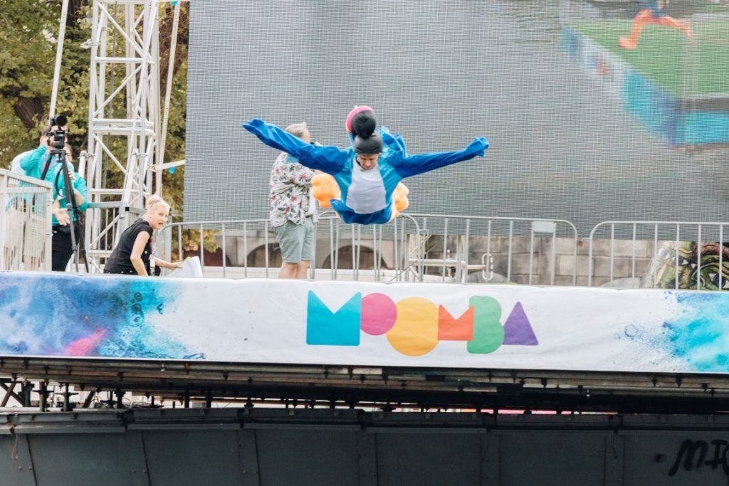 A man in a blue costume jumping off a stage into some water