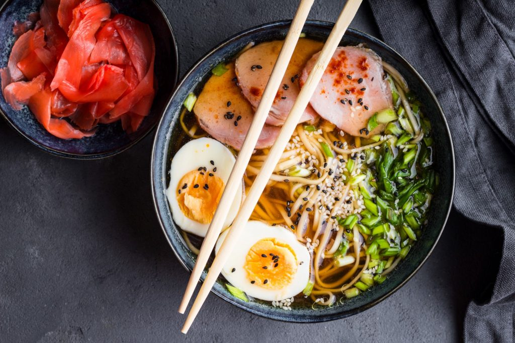 Traditional Japanese soup ramen with meat broth, asian noodles, seaweed, sliced pork, eggs and ginger on dark concrete background. Close up. Asian style food. Top view.