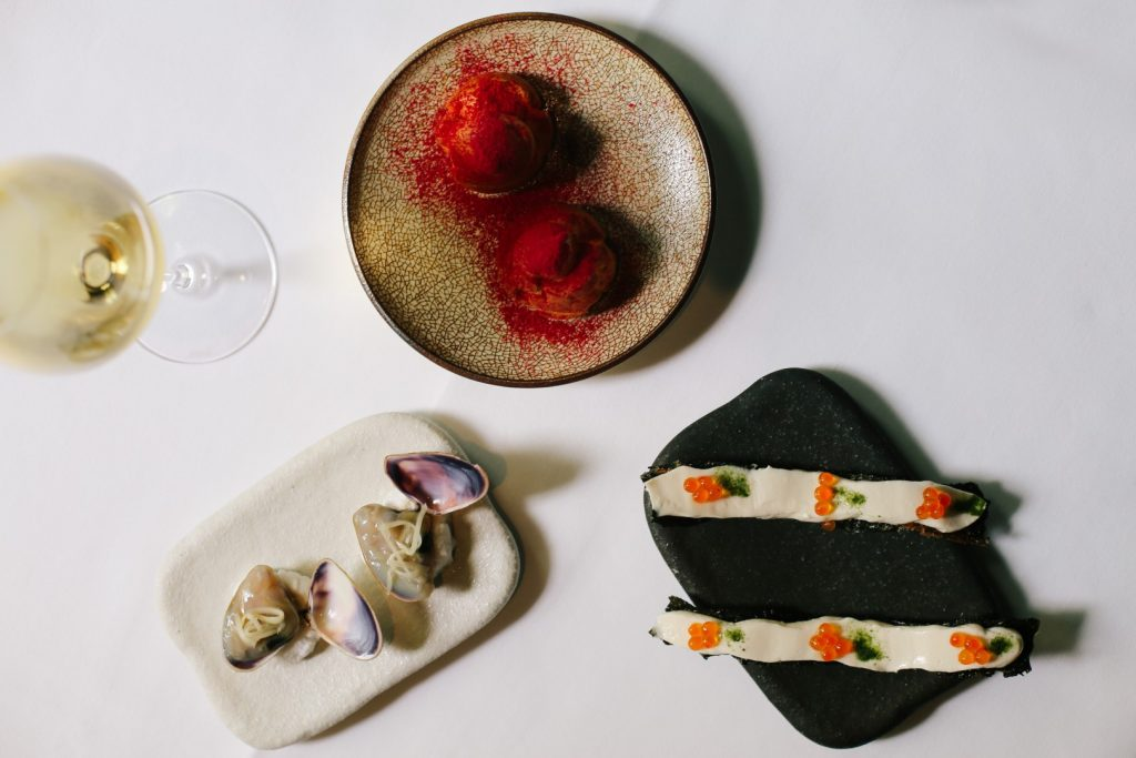 A top down shot of three plates with food on them on a white table cloth