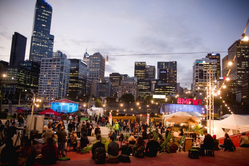 A night time scene with people at a large event with the city skyline in the background