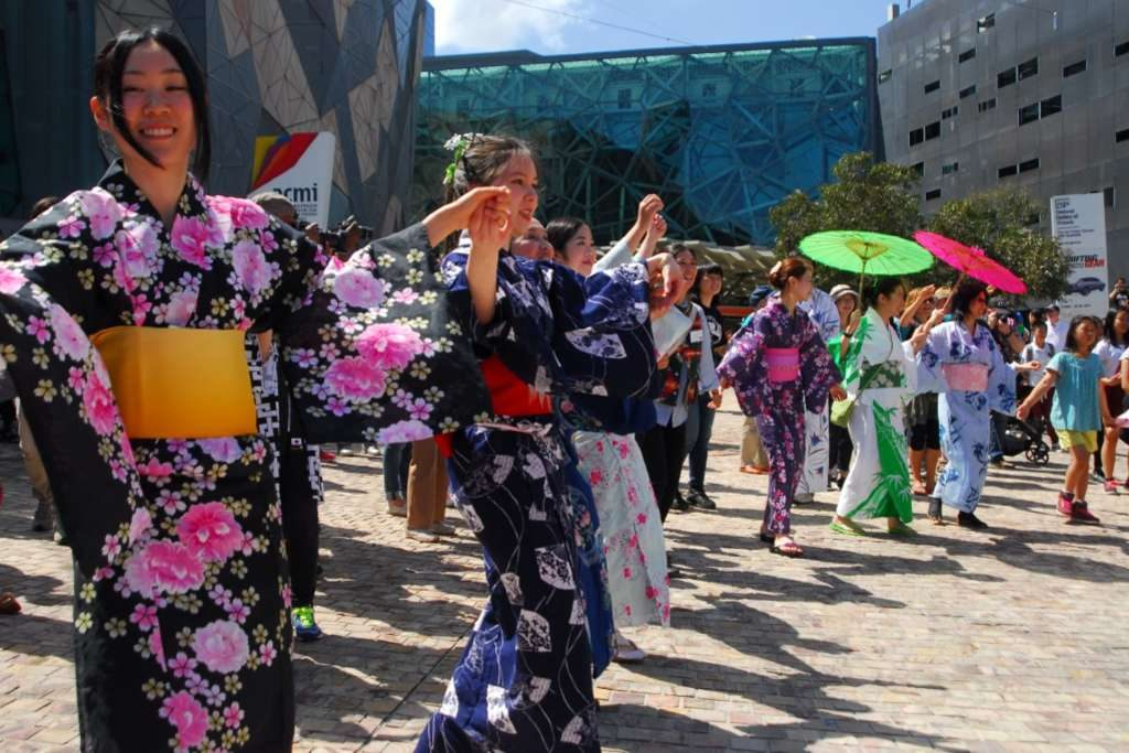 A group of women dressed in kimonos dancing in an outdoor square