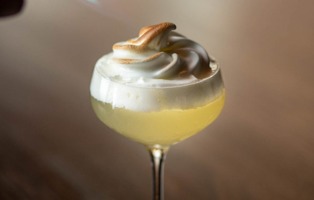 A tall cocktail glass with lemon coloured liquid in it, topped with a whipped white meringue