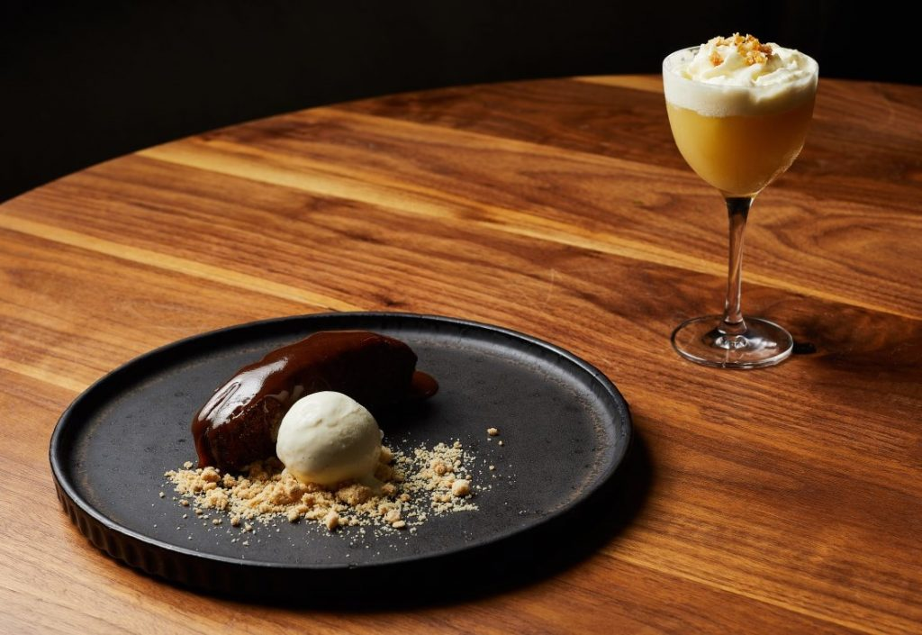 A sticky date ice cream dessert on a plate next to a cocktail
