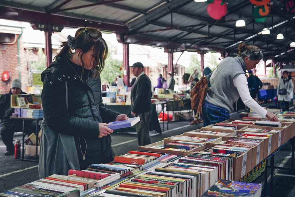 A woman browsing stalls of books at a market