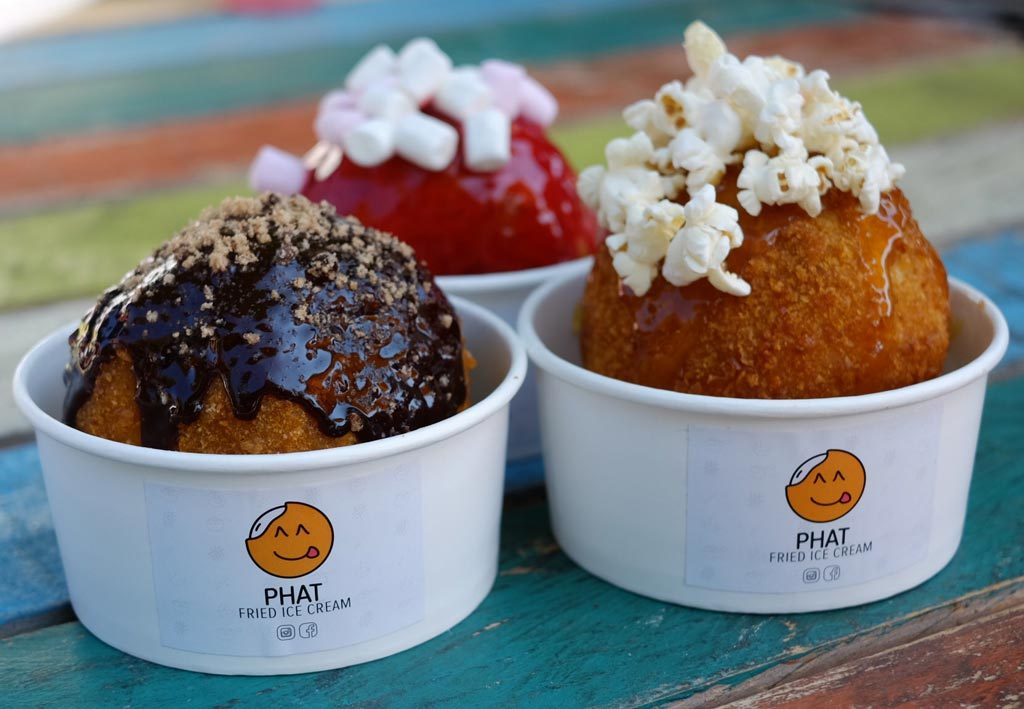 Three containers with fried ice cream in them topped with popcorn and different sweet sauces