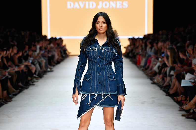A model at the end of the runway, centred in front of the camera, wearing a short denim skirt and matching long denim shirt