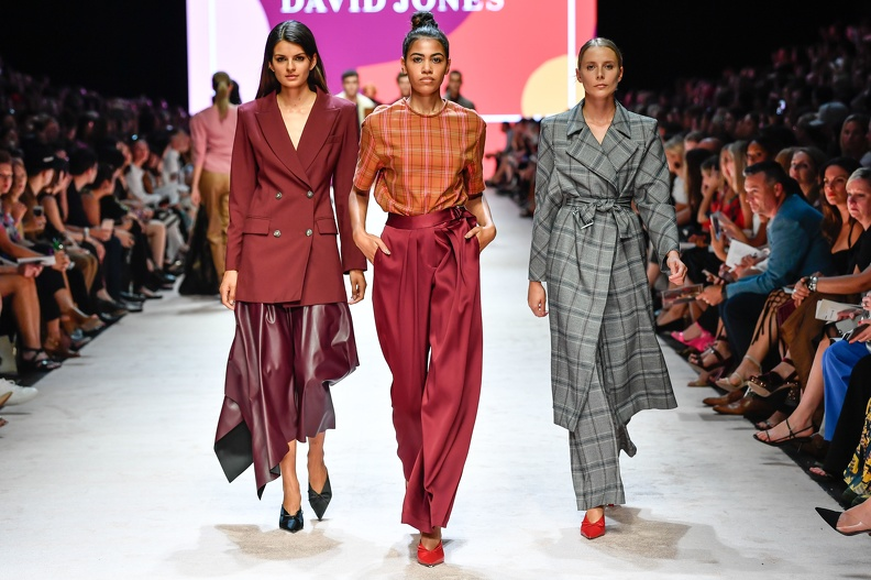 Three models at the end of a runway wearing skirts and jackets with plaid designs