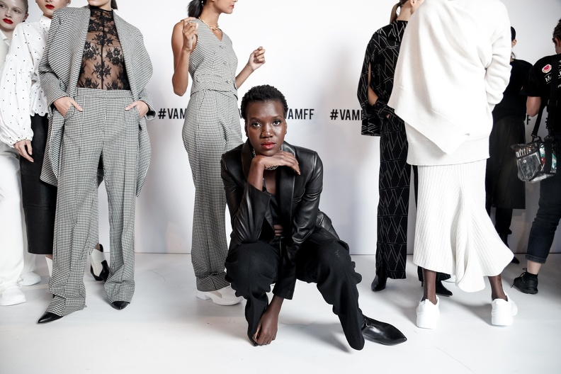 A line of models in white and black outfits in front of a white wall, one model dressed in black crouches down on the ground and looks at the camera.