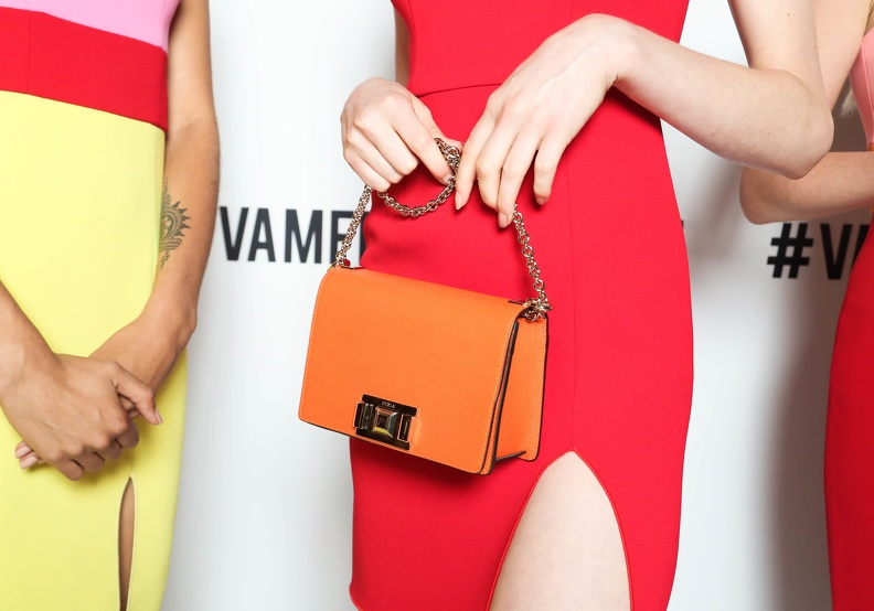 A woman's torso, dressed in a red dress holding a bright orange bag in front of her.