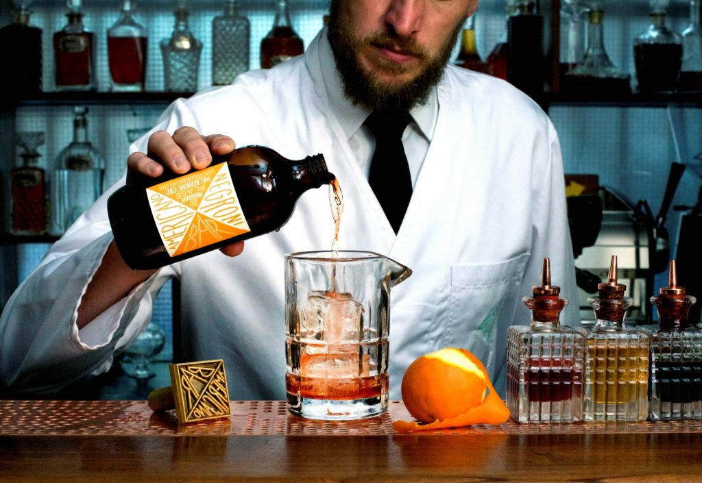 A man in a white coat pours a bottle of alcohol into a glass beaker
