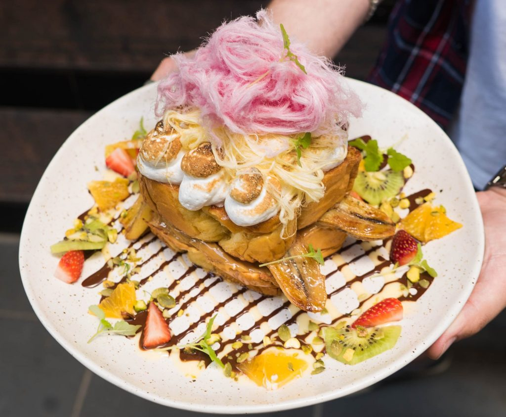 A white plate stacked with french toast, covered in fruit and meringue with fairy floss on top