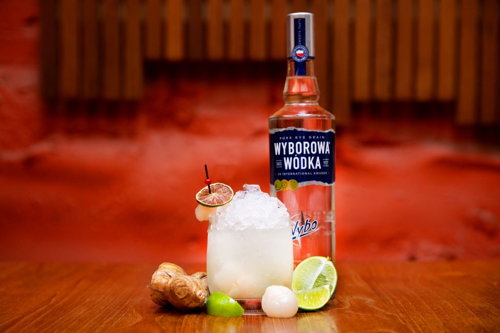 A bottle of alcohol on a table with a cocktail in front of it, and slices of lime and other fruits around it