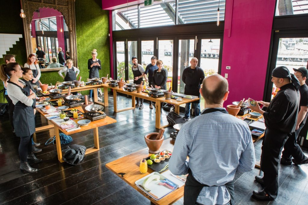 People standing at tables doing a workshop inside a room with floor to ceiling windows