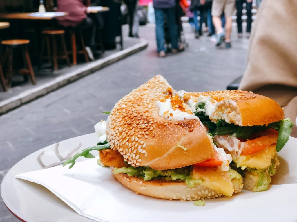 A bagel on a plate with lettuce and tomato inside it