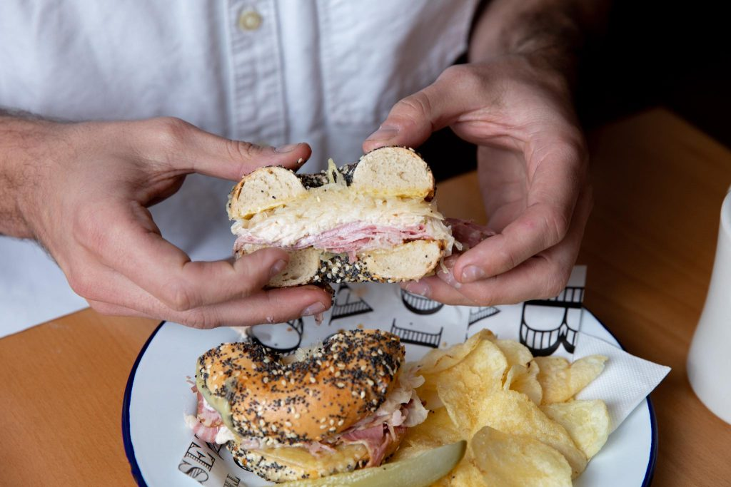 Person holding half a bagel with corned beef, cheese and sauerkraut inside. Pickle and chips on the side of the plate.