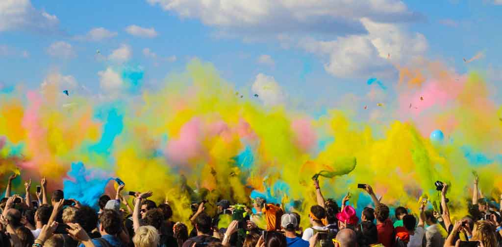 People throwing colourful powder in the air at a cultural event
