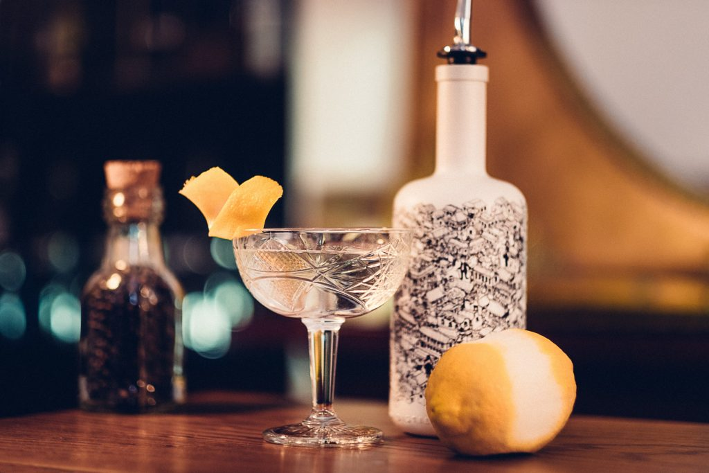 A martini glass, bottle of gin and a lemon on a wooden bench