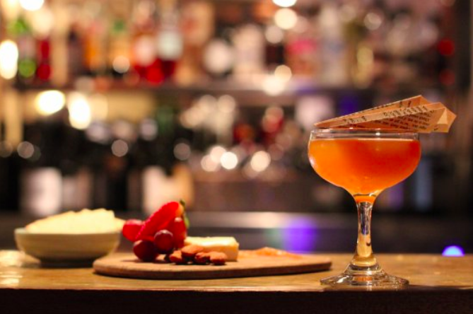 orange cocktail with paper plane on top, and cheese board and bar in background