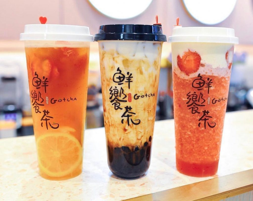 Three cups of milk tea and bubble tea on a wooden bench