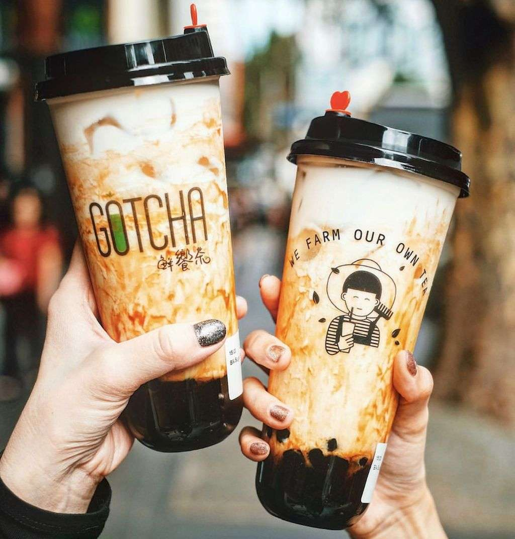 Two bubble tea cups clinking together