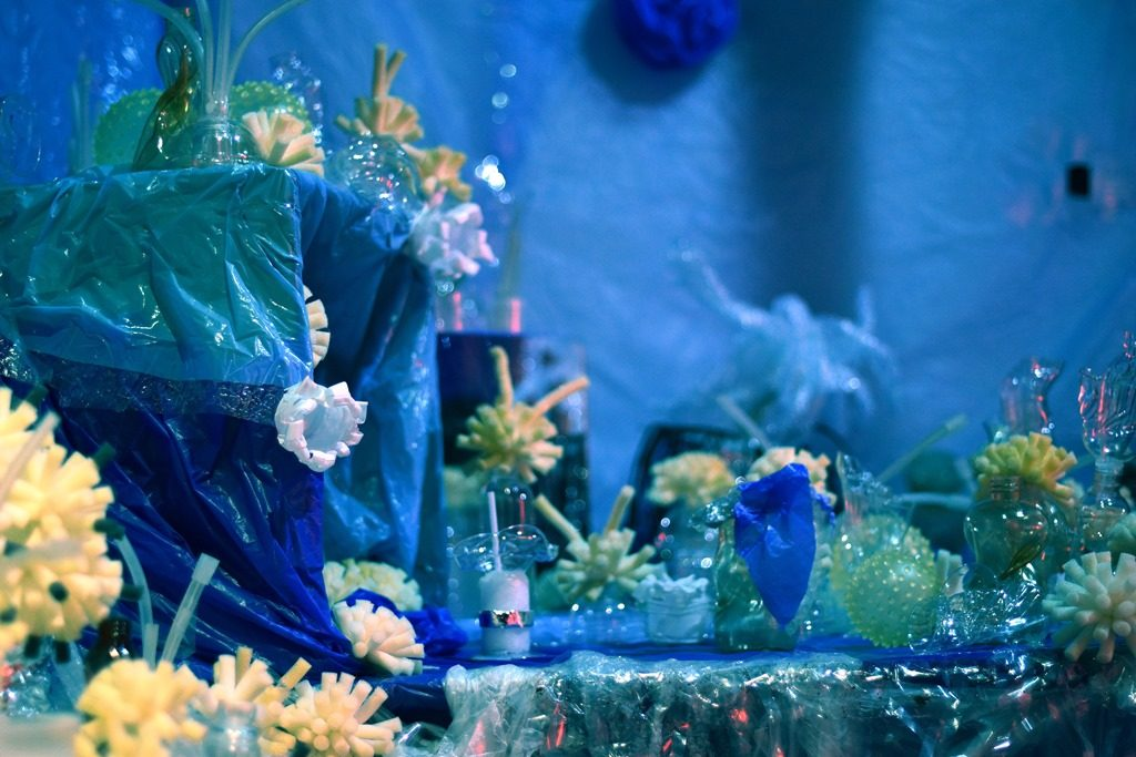 A large diorama artwork of an underwater coral reef scene made of lots of different recycled plastic and glass