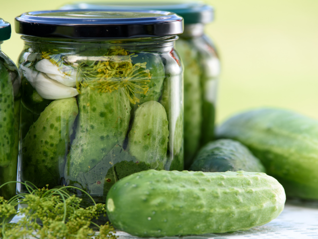 two jars of pickles and gherkins sitting on a table