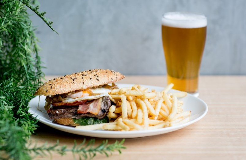 A steak sandwich on a table with french fries and a glass of beer