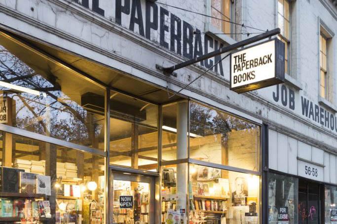 A woman walking past a bookshop