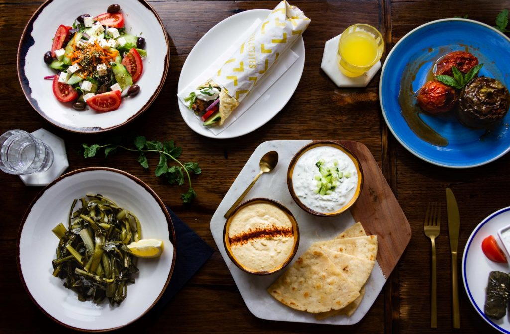 A flatlay of Greek food on a wooden table
