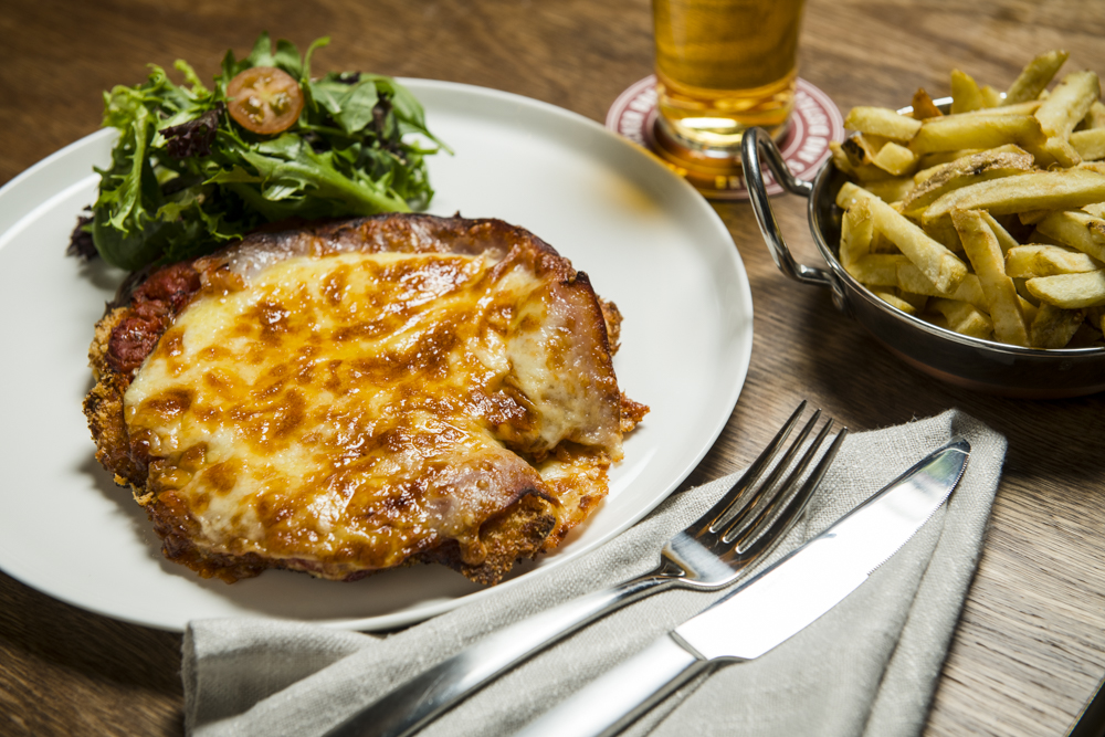 A chicken parmigiana on a white plate with a side dish of chips
