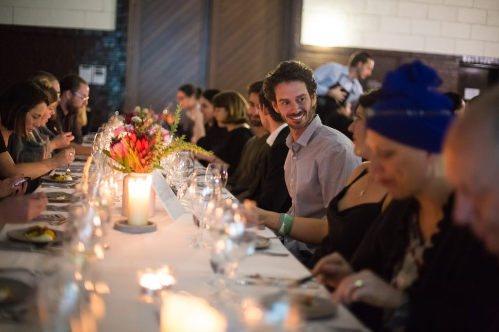 A group of people sitting and talking at a long dinner table with candles